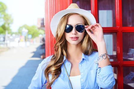 gafas de sol: Mujer joven hermosa que recorre en la ciudad Foto de archivo