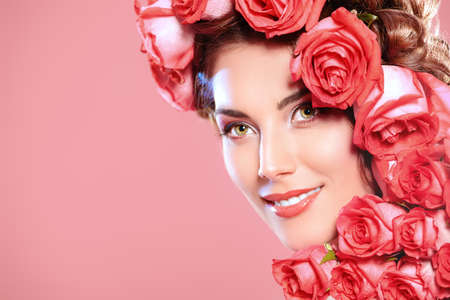 Beautiful tender girl with floral hairstyle. Roses. Cosmetics. Beauty, fashion. Spring and summer. Copy space. photo