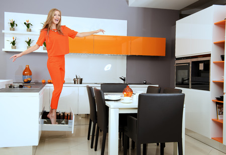 quality home: Cheerful young woman demonstrates the high quality of the kitchen furniture. Home interior.