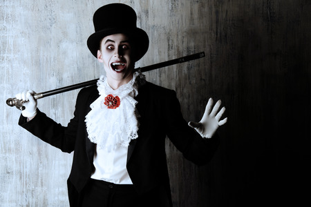 vampire: Handsome male vampire in a tail-coat and top-hat. Halloween. Dracula costume. Stock Photo
