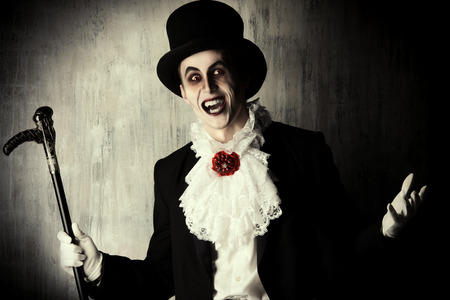 dracula: Handsome male vampire in a tail-coat and top-hat. Halloween. Dracula costume. Stock Photo