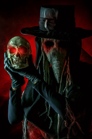 plague: Medieval plague doctor stands with a skull. Medieval Europe. Halloween.