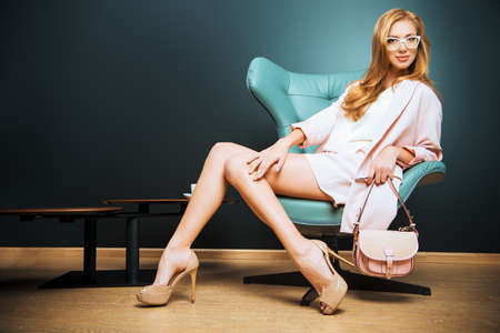 shoe model: Portrait of a beautiful fashionable model sitting in a chair in Art Nouveau style. Interior, furniture.