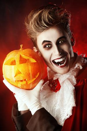 calabazas de halloween: Retrato de un vampiro guapo con calabaza. Halloween. Traje de Dr�cula.