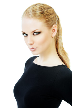 Close-up portrait of a beautiful young woman with smoky eyes make-up wearing black fitting clothing. Beauty, fashion. Body care. Isolated over white. photo