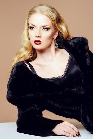 woman in fur coat: Beautiful blonde woman wearing mink fur coat. Fashion, beauty. Luxurious lifestyle. Studio shot. Stock Photo