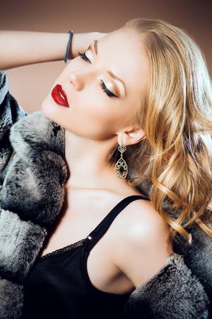 manteau de fourrure: Mode de tir une belle femme blonde portant des bijoux et manteau de fourrure. Studio, coup.