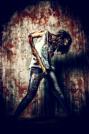 bloodthirsty: Scary bloody zombie girl with an ax. Halloween.