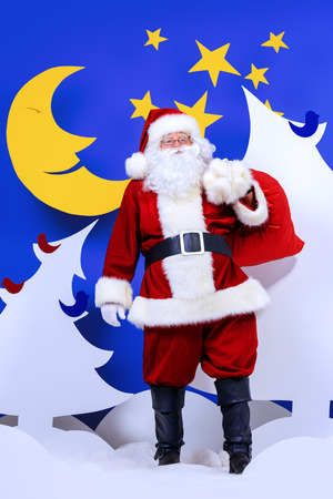 full length portrait: Santa Claus standing with his bag of giftsin a cartoon fairy snowy forest. Full length portrait.