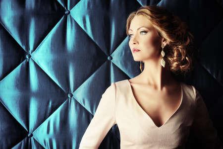 Retrato de una mujer hermosa en vestido de noche elegante que presenta sobre el fondo de la vendimia. Joyería. Disparo de moda. Peinado.