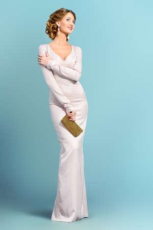 traje de gala: Retrato de cuerpo entero de una mujer hermosa en vestido de noche elegante posando sobre fondo gris. Disparo de moda. Peinado.