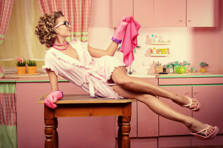 alluring: Sexy pin-up girl wearing pink bathrobe alluring on her pink kitchen at home. Fashion. Full length portrait. Stock Photo