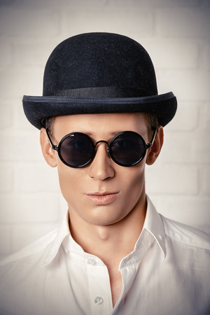 fop: Fashion shot of a modern young man in white shirt, black bowler hat and round sunglasses.