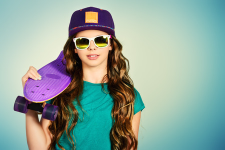 fashionable sunglasses: Pretty girl teenager wearing casual clothes posing with her skateboard. Active lifestyle. Studio shot.
