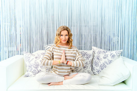 yoga pillows: Happy young woman having a rest in her bedroom and doing yoga exercises Stock Photo