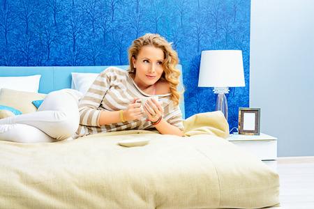 bedspread: Happy elegant woman having a rest in her bedroom Stock Photo