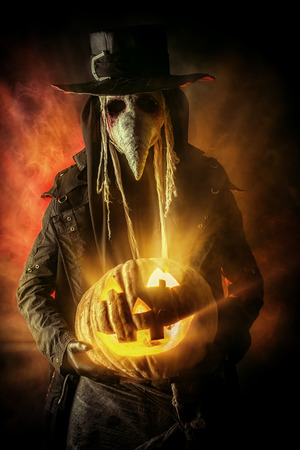 medieval medicine: Frightening plague doctor stands with a pumpkin Stock Photo