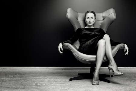 Черно-белый портрет потрясающей модной модели, сидя в кресле в стиле модерн