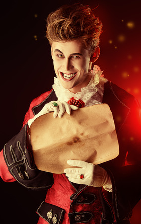frightening: Attractive and frightening vampire holding a Sheepskin Scroll Stock Photo