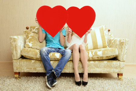 red couch: Romantic young couple sitting relaxed on a sofa in the cozy living room of their home hold big red hearts