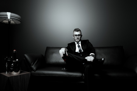 고급스러운 인테리어에 가죽 소파에 앉아 마시는 레드 와인 우아한 정장에 잘 생긴 성숙한 남자의 흑백 초상화.