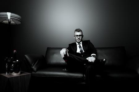 suit: Retrato en blanco y negro de un hombre maduro guapo en traje elegante beber vino rojo, sentado en un sofá de cuero en un interior de lujo.