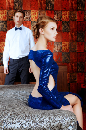 Beautiful woman and young man in elegant evening dresses in a classic interior photo