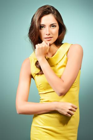 Beautiful young woman in elegant dress posing at studio