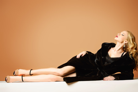 laying: Beautiful blonde woman wearing mink fur coat. Fashion, beauty. Luxurious lifestyle. Studio shot. Stock Photo