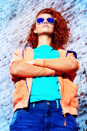glass brick: Young stylish girl in the city. Brick wall background. Youth fashion. Hip-hop style. Stock Photo