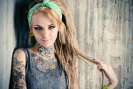 tatouage sexy: Sexuelle fille blonde posant avec des dreadlocks fascinants par le mur grunge. Pin-up de style.