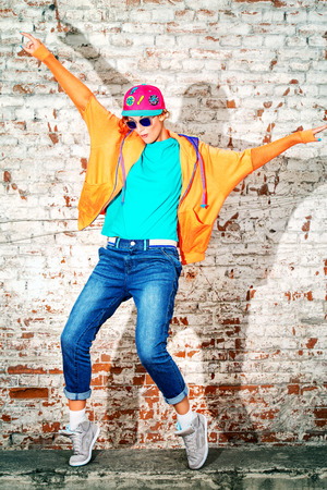 Young stylish girl in the city. Brick wall background. Youth fashion. Hip-hop style. Stock Photo