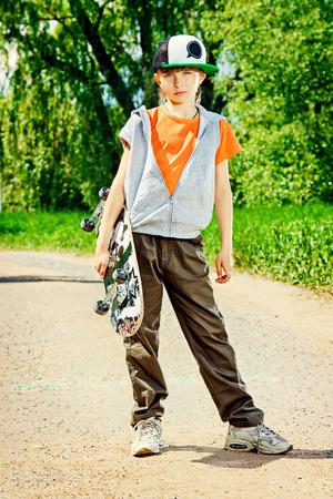ni�o en patines: Muchacho adolescente fresco con su patineta en la calle. Ni�ez. Summertime. Foto de archivo