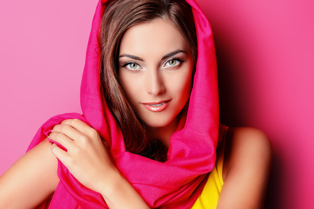 cosmetic: Beauty portrait of a positive young woman in bright crimson headscarf over pink background. Beauty, fashion. Cosmetics. Stock Photo