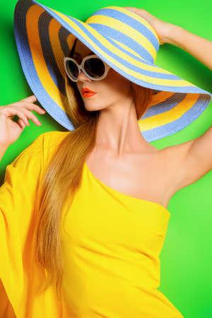 moda: Senhora elegante bonita usando um vestido amarelo brilhante sobre o fundo verde