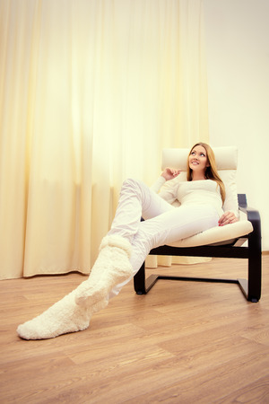 comfortable chair: Happy young woman resting at home in a comfortable chair. Stock Photo
