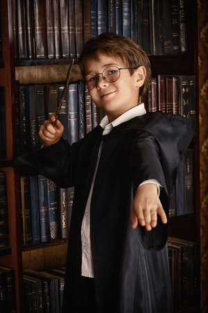 wizard: A boy stands with magic wand in the library by the bookshelves with many old books