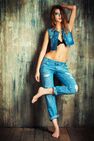eyewear fashion: Full length portrait of an attractive girl in casual jeans clothes standing by the grunge wall Stock Photo