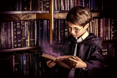 Smart boy stands in the library by the bookshelves with many old books