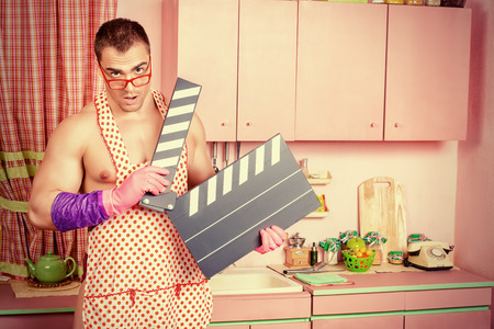 householder: Muscular young man in an apron posing in the pink kitchen with cinema clapperboard.