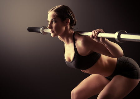 Strong young woman with beautiful athletic body doing exercises with barbell Stock Photo
