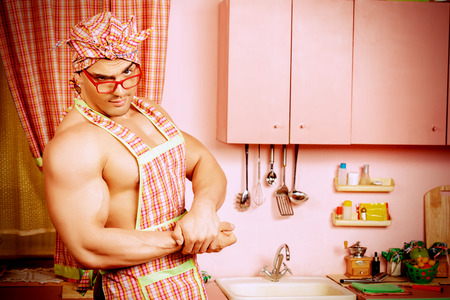 householder: Handsome muscular man in an apron cooking in the pink kitchen