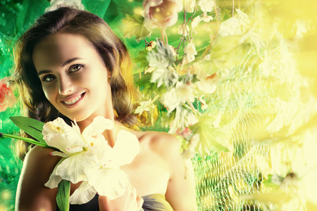 bronzed: Happy beautiful brunette woman among summer plants and flowers Stock Photo
