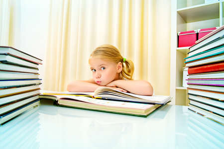 five year old: Five year old girl sitting at table at home with piles of books and dreams. Educational concept.
