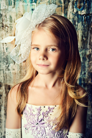 Art portrait of a pretty little girl wearing princess dress and elegant hat. Fashion shot. Childhood.