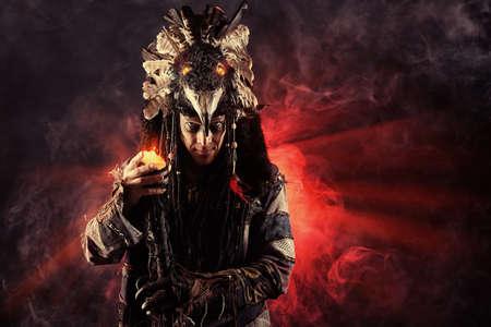 guerrero: Retrato de un cham�n masculino en traje t�pico rodeado de niebla. Concepto de la fantas�a, la magia.