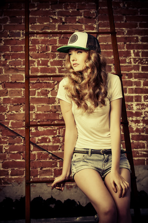 shorts t shirt sexy: Beautiful modern girl near the brickwall in the rays of the evening sun. Youth style. Fashion shot. Stock Photo