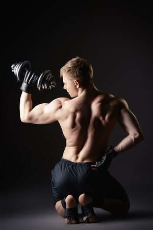 male arm: Athlete man doing exercises with dumbbells. Bodybuilding. Muscles of the arms and back. Studio shot over black background.