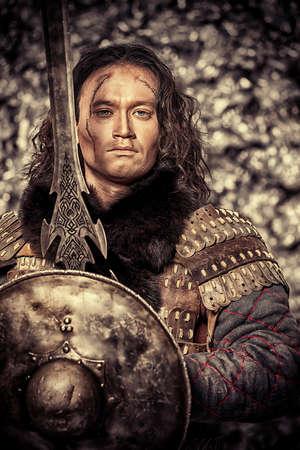 espadas medievales: Guerrero masculino antigua en la armadura que sostiene la espada y el escudo. Personaje hist�rico. Fantas�a.