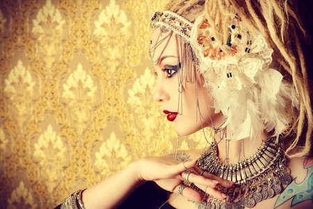 taniec: Close-up portret wspaniałego tradycyjnego tancerka na złotym tle rocznika. Taniec etniczny. Taniec brzucha. Tribal taniec. Make-up, kosmetyki. Zdjęcie Seryjne